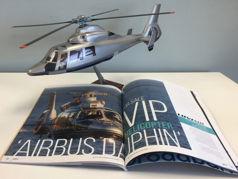 """Small scale model of AS365N3 Helicopter behind an open magazine with helicopter picture on it, showing """"VIP Helicopter: Airbus Dauphin"""""""